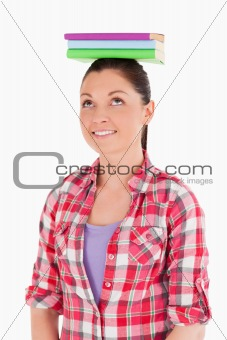 Beautiful female holding books on her head while standing