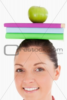 Beautiful female holding an apple and books on her head while st