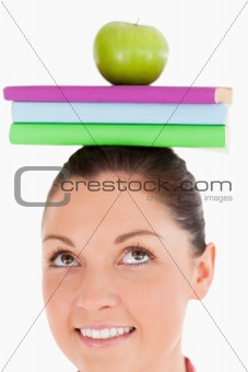 Attractive female holding an apple and books on her head while s