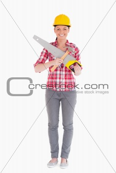 Beautiful woman holding a saw while standing