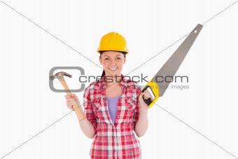 Attractive woman holding a saw and a hammer while standing