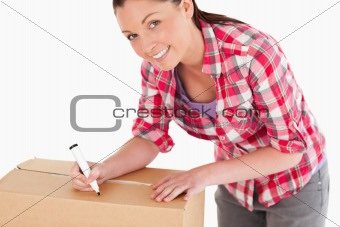 Portrait of an attractive woman writing on cardboard boxes with