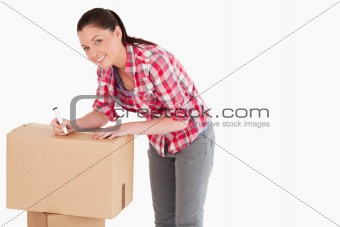 Beautiful woman writing on cardboard boxes with a marker while s