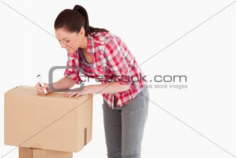Attractive woman writing on cardboard boxes with a marker while