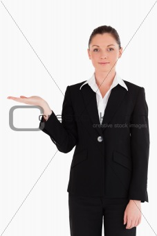 Attractive woman in suit showing a copy space while standing