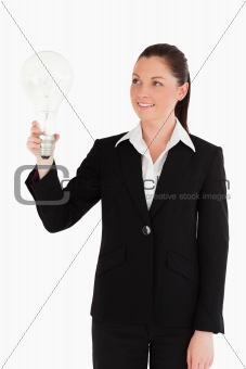 Beautiful woman in suit holding a light bulb while standing