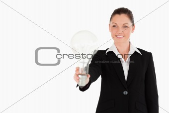 Charming woman in suit holding a light bulb while standing