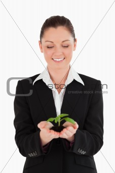 Attractive woman in suit holding a small plant