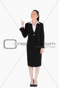 Attractive female in suit pointing at a copy space