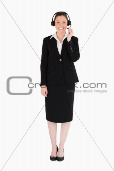 Beautiful woman in suit using headphones and posing
