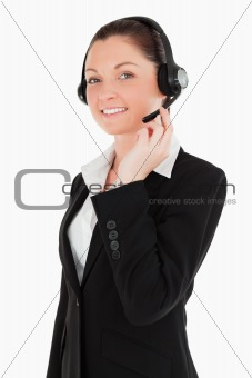 Portrait of an attractive woman in suit using headphones and pos