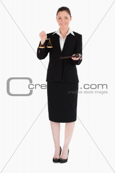 Attractive woman in suit holding scales of justice and a gavel