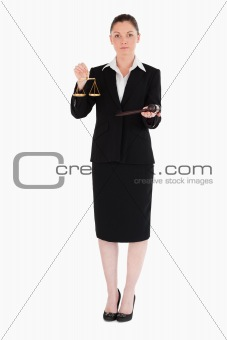 Charming woman in suit holding scales of justice and a gavel