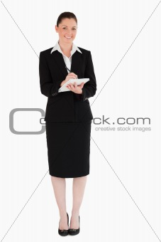 Charming woman in suit writing on a notebook