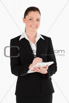Portrait of an attractive woman in suit writing on a notebook