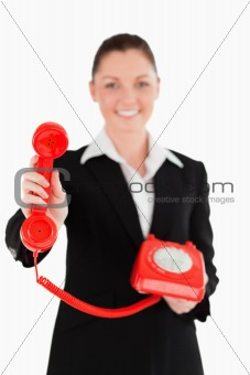 Beautiful woman in suit holding a red telephone