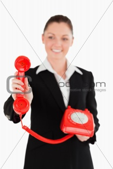 Attractive woman in suit holding a red telephone