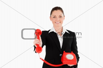 Charming woman in suit holding a red telephone