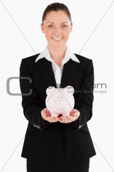 Beautiful woman in suit holding a pink piggy bank
