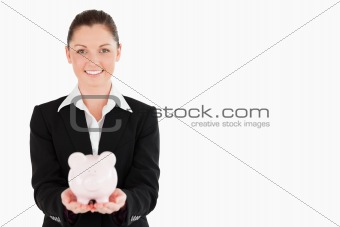 Charming woman in suit holding a pink piggy bank