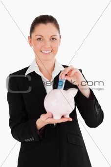 Charming woman in suit inserting a money bill in a pink piggy ba
