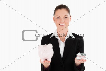 Beautiful woman in suit holding a piggy bank and a miniature hou