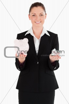 Attractive woman in suit holding a piggy bank and a miniature ho