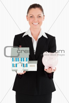 Charming woman in suit holding a piggy bank and a miniature hous