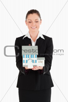 Beautiful woman in suit holding a miniature house