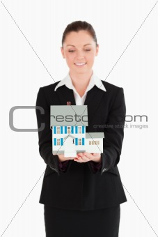 Attractive woman in suit holding a miniature house