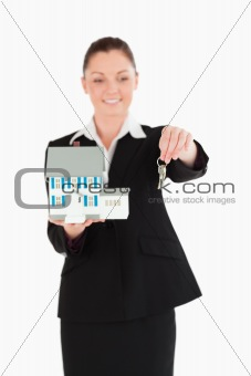 Beautiful woman in suit holding keys and a miniature house