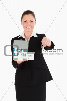 Attractive woman in suit holding keys and a miniature house