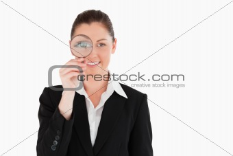 Charming woman in suit holding a magnifying glass