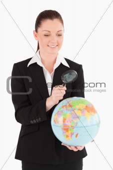 Beautiful female in suit holding a globe and using a magnifying
