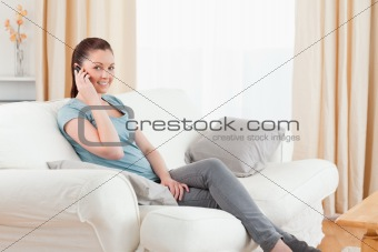 Attractive woman on the phone while sitting on a sofa