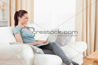 Attractive woman relaxing with her laptop while sitting on a sof