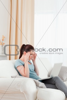 Beautiful upset woman gambling with her computer while sitting o
