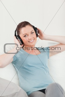 Cute woman relaxing with headphones while sitting on a sofa