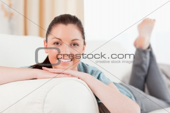 Attractive woman posing while lying on a sofa