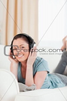 Attractive woman with headphones posing while lying on a sofa