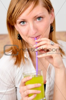 Beautiful young woman drinks juice
