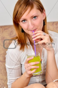 Beautiful young woman drinks juice