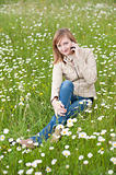 Beautiful young woman siting on a grass field in park and talkin