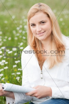 Beautiful young woman reading a book outdoors on a grass field