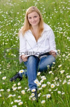 Beautiful young woman reading a book outdoors on a grass field i