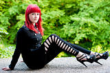 Sexy young girl with red hair in black dress rests in park