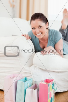 Charming woman posing while lying on a sofa