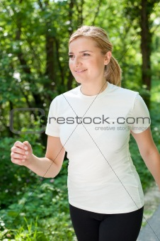 Cute active woman on a walk through forest