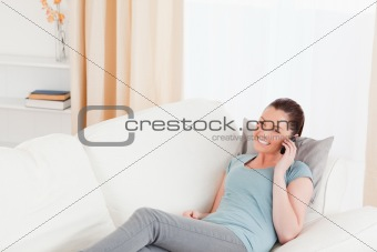 Attractive woman on the phone while lying on a sofa