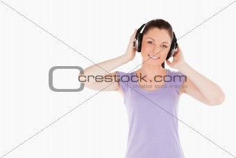 Charming woman posing with headphones while standing